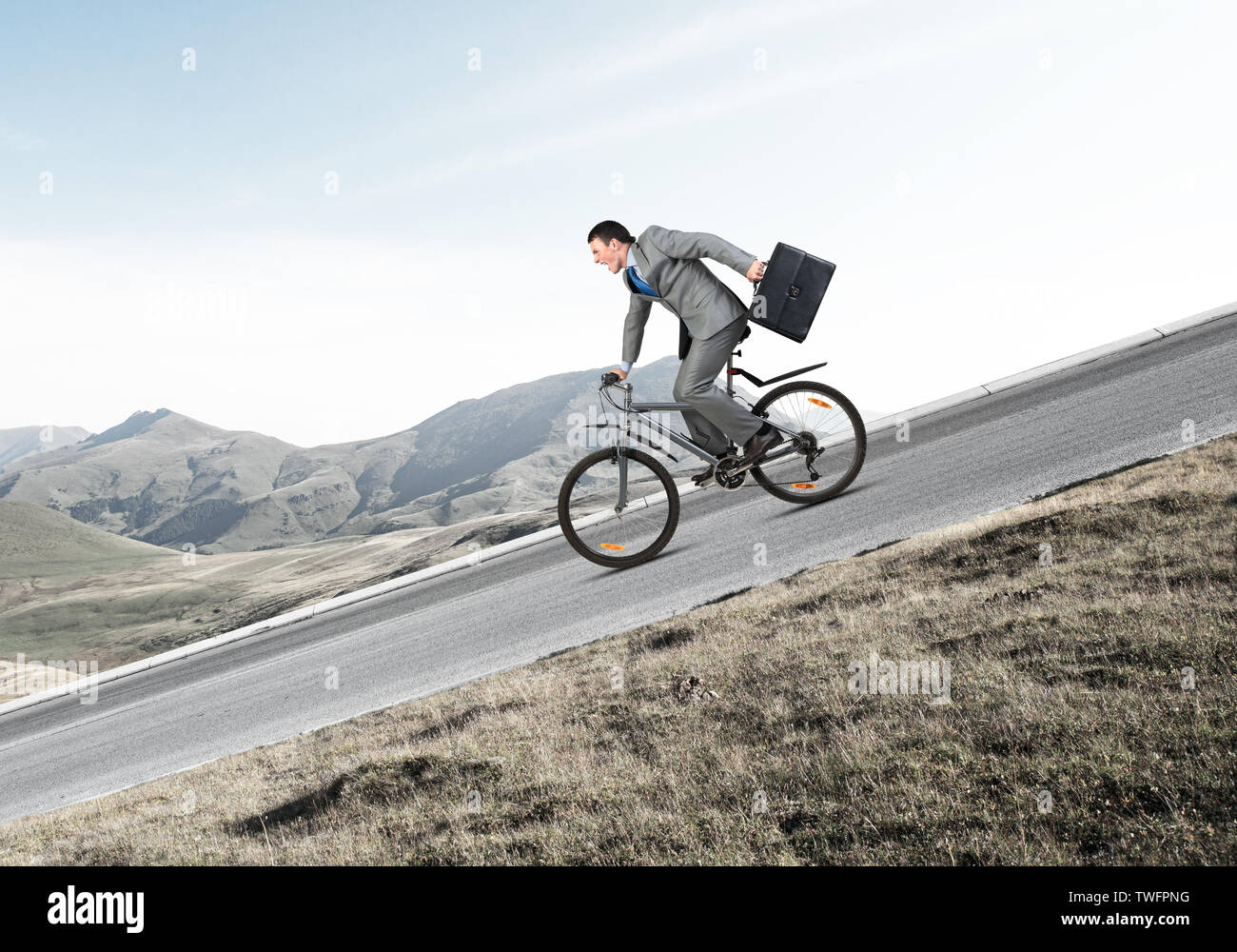 Young Man On Bicycle Fast Riding Downhill At Sunny Day