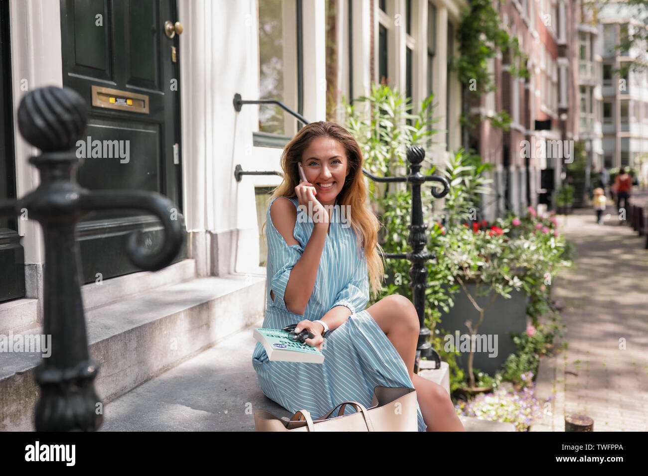 Woman in blue long dress sitting on the steps outdoor near the green door. Long curly blue hair, daily makeup.Big smile. white teeth. Talking by phone Stock Photo