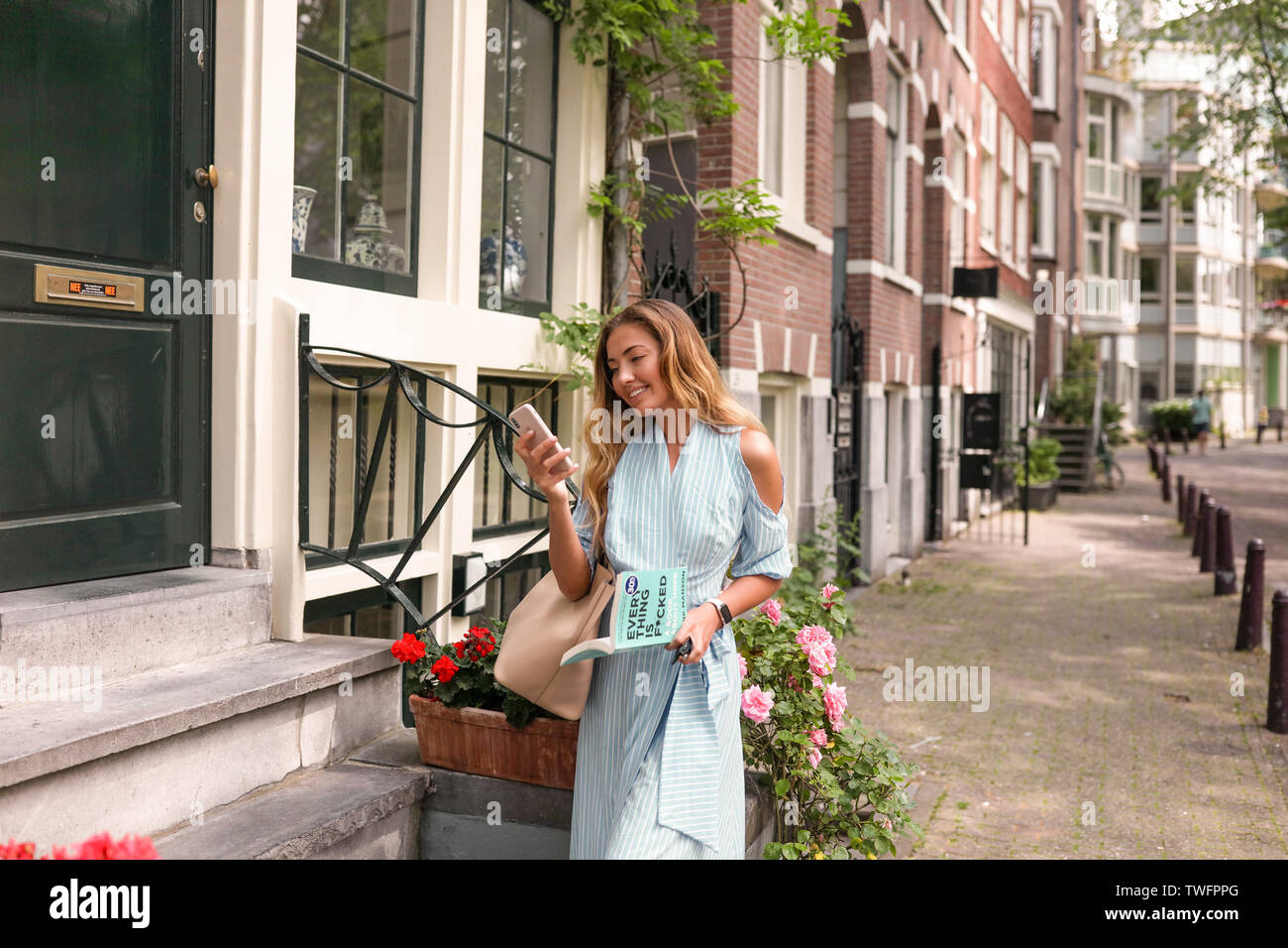 Sexy girl walking alone on the colorful european streets. Holding a phone in her hand and smiling, book in another hand. Stylish blue dress and pink Stock Photo
