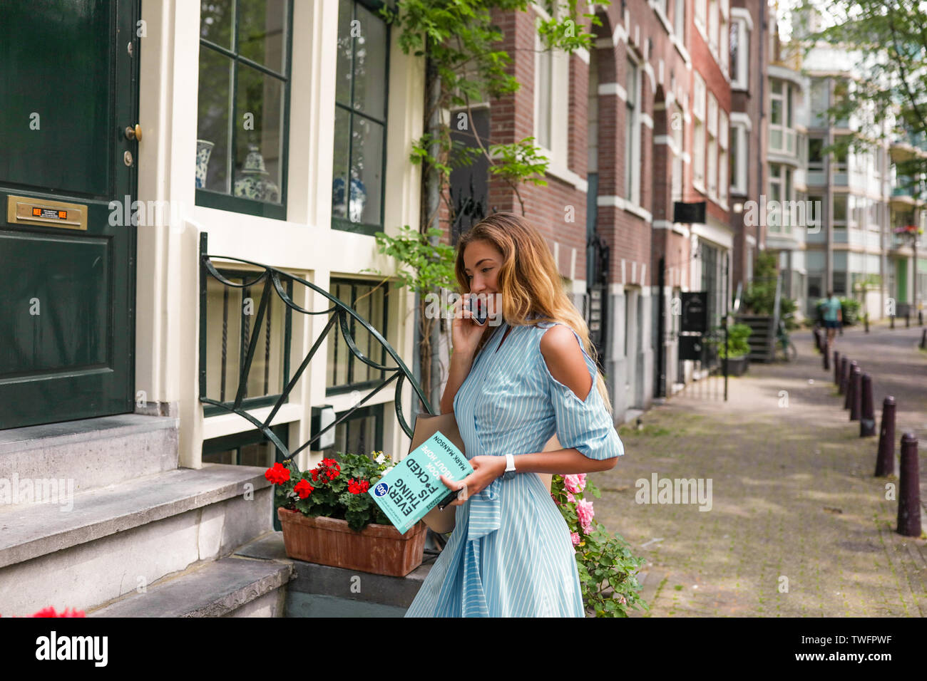 Gently skin and cute blue dress with open shoulders. Lady talking on the phone with her man, smiling and flirting. Holding a book in her hand, standin Stock Photo