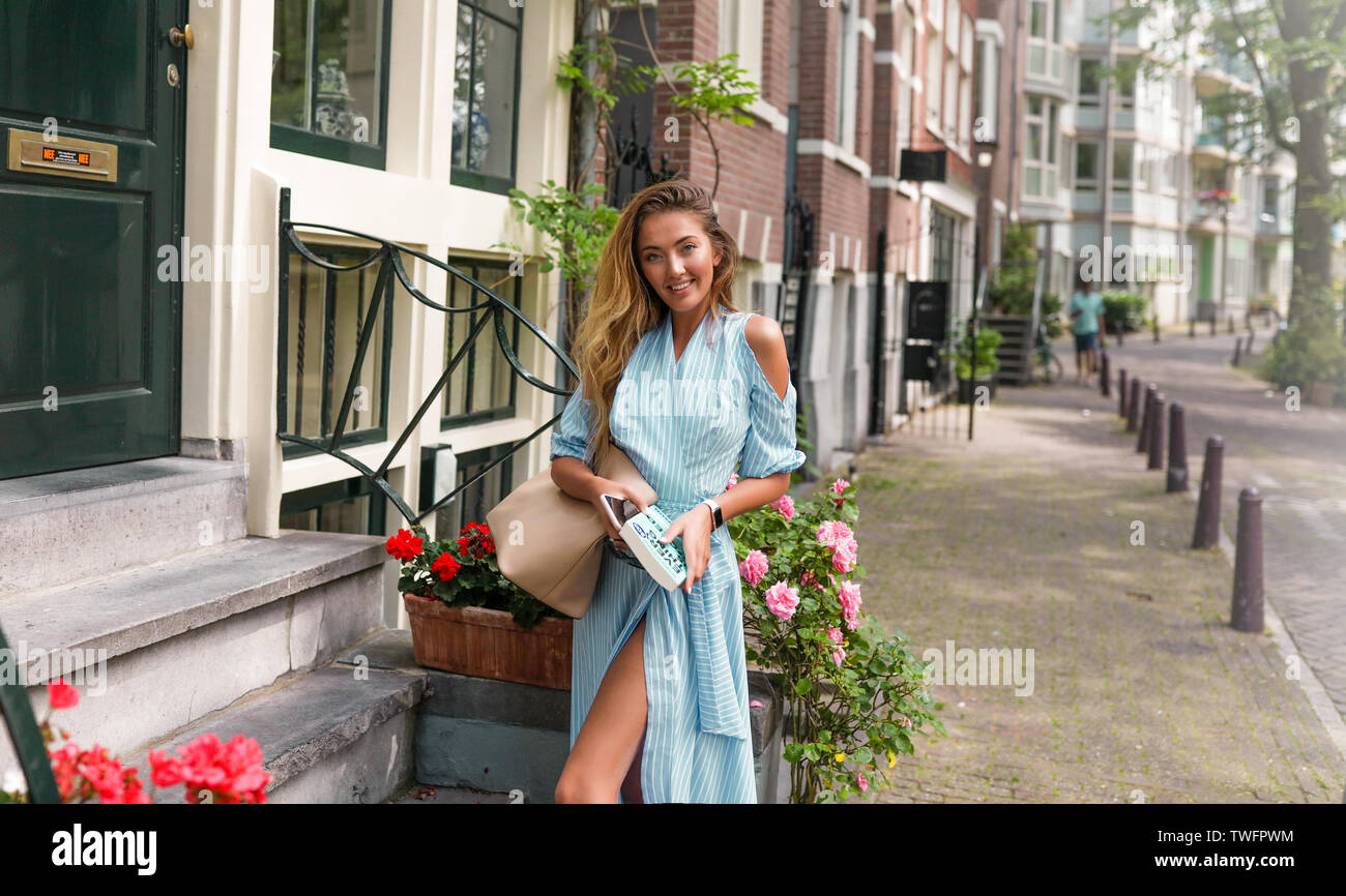 Woman travelling around the world, enjoys her vacation from work. Posing on the flowers background on the street.Stylish look, blue modern dress, pink Stock Photo