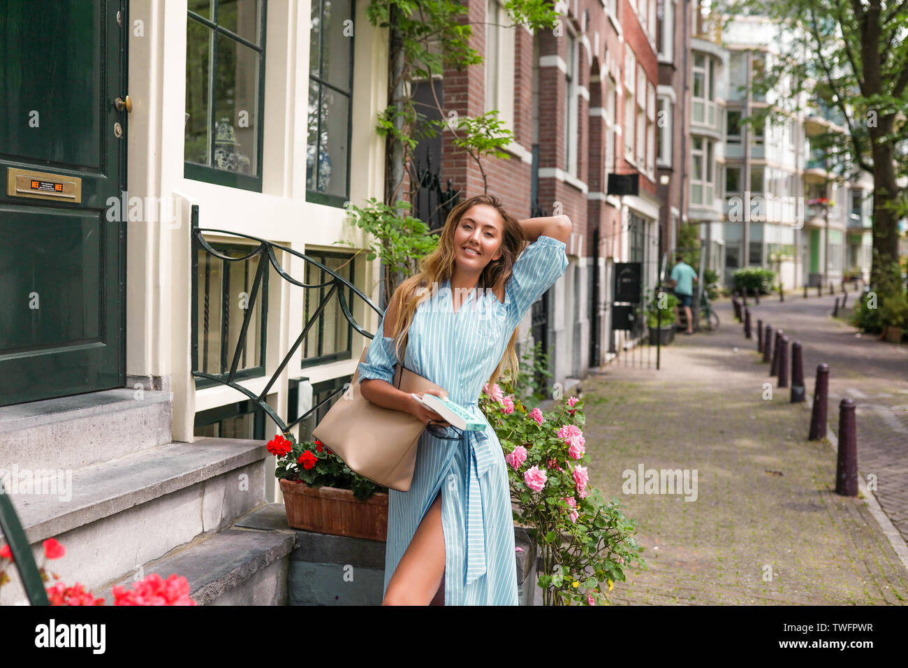 Funny girl shooting near the flowers, bright europenean streets, standing near the green door.Slim sexy body in modern summer dress with open shoulder Stock Photo