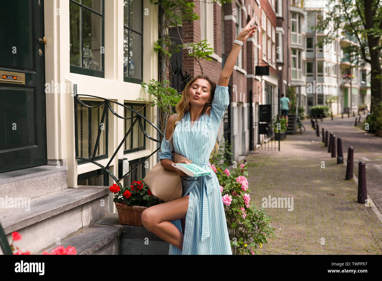 Bright young woman having fun outdoor, raised her hand, showing leg. Pretty face with makeup, volume stylish hair. Wearing long blue dress with waist Stock Photo