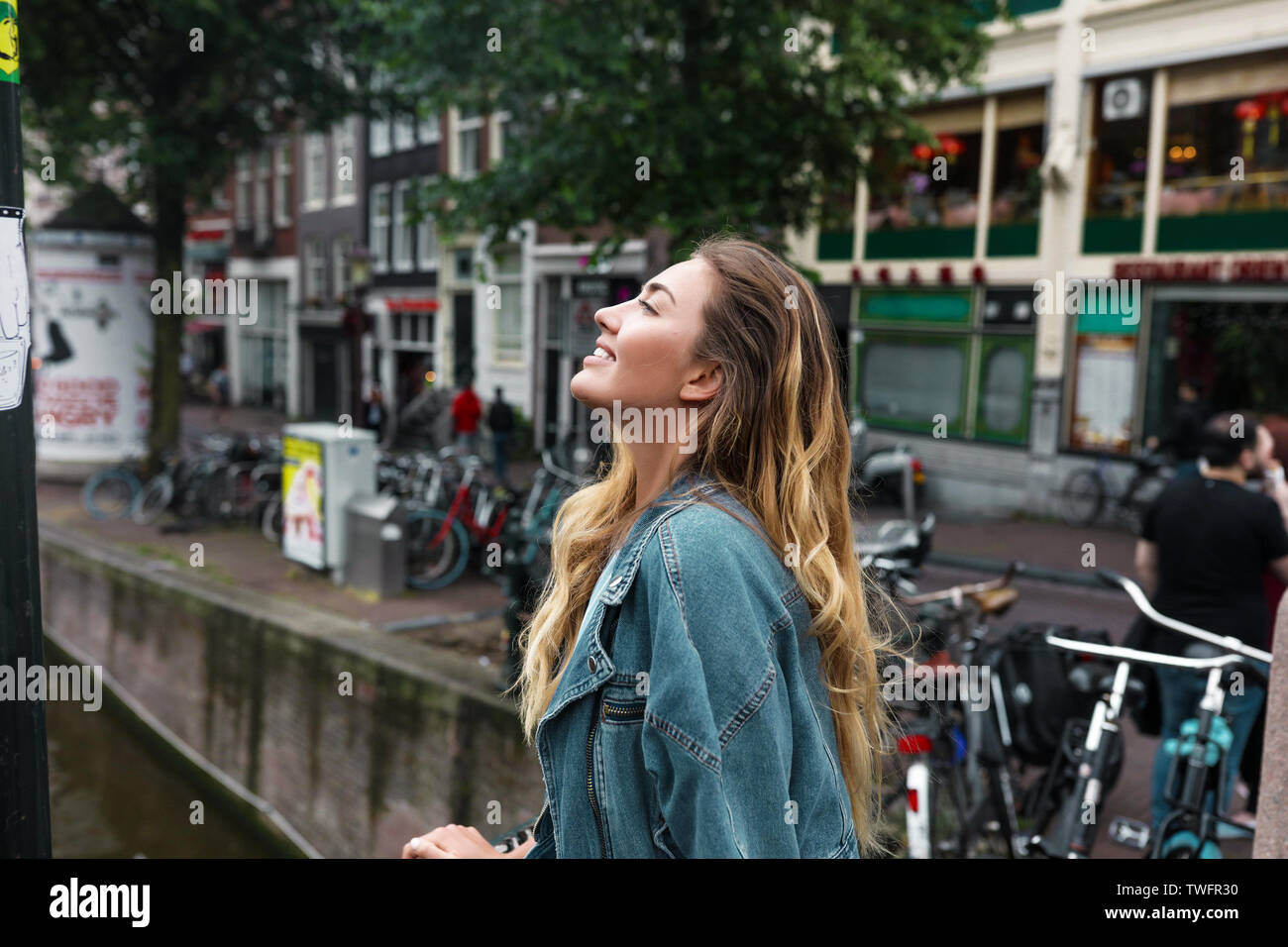 Cute girl in jeans jacket standing outdoor on the bridge and looking far away, thinking of her travellings. Long hairstyle, nude makeup, white teeth. Stock Photo