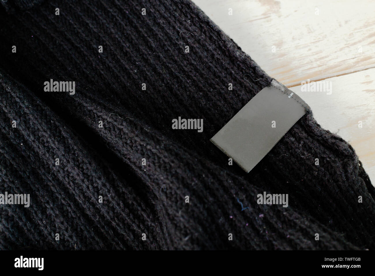 Stack of wool knitted warm sweater and white label for text - Stock Image