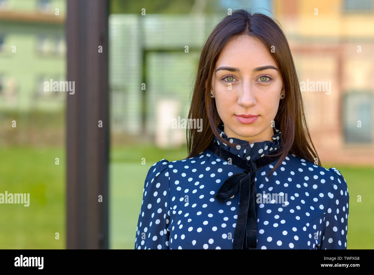 Serious demure stylish young woman in a stylish blue and white outfit staring at the camera against window reflections and copy space - Stock Image