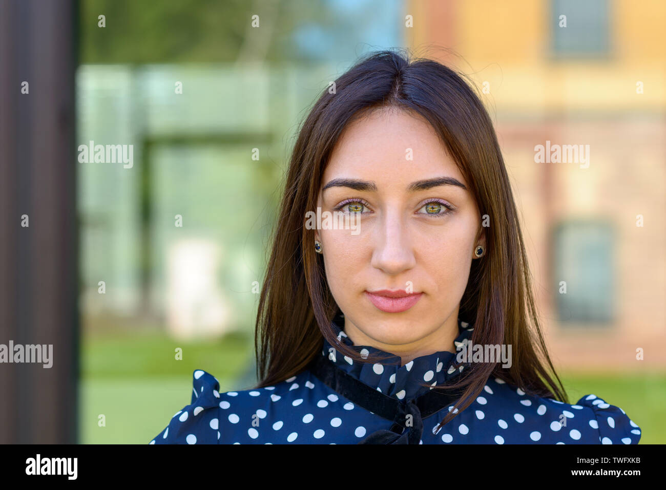 Close up of an serious demure stylish young woman in a stylish blue and white outfit and copy space - Stock Image