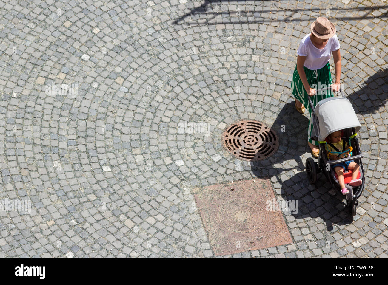 Mother pushing baby buggy against cobble stone pavement shot from the Heroes Tower, Kőszeg, Hungary - Stock Image