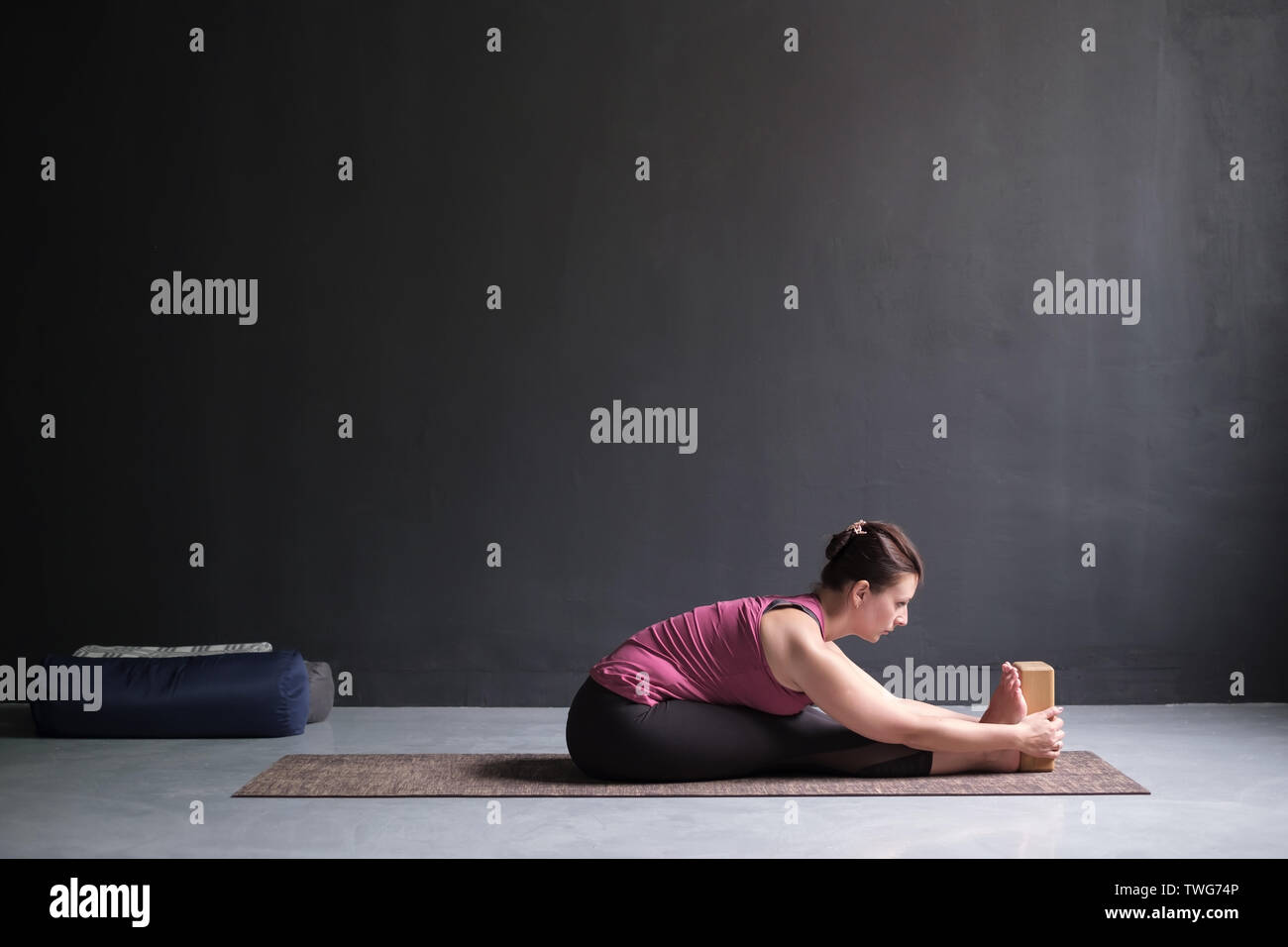 Woman practicing yoga, doing Seated forward bend pos - Stock Image