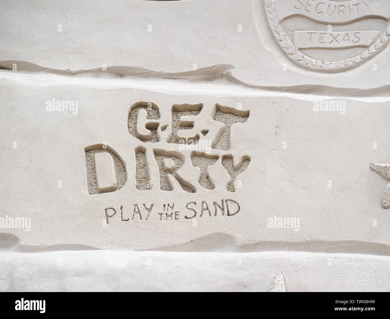 ' Get Dirty Play in the Sand,' slogan from Texas Sandfest 2019 sculpted in sand, closeup. Port Aransas, Texas USA. - Stock Image