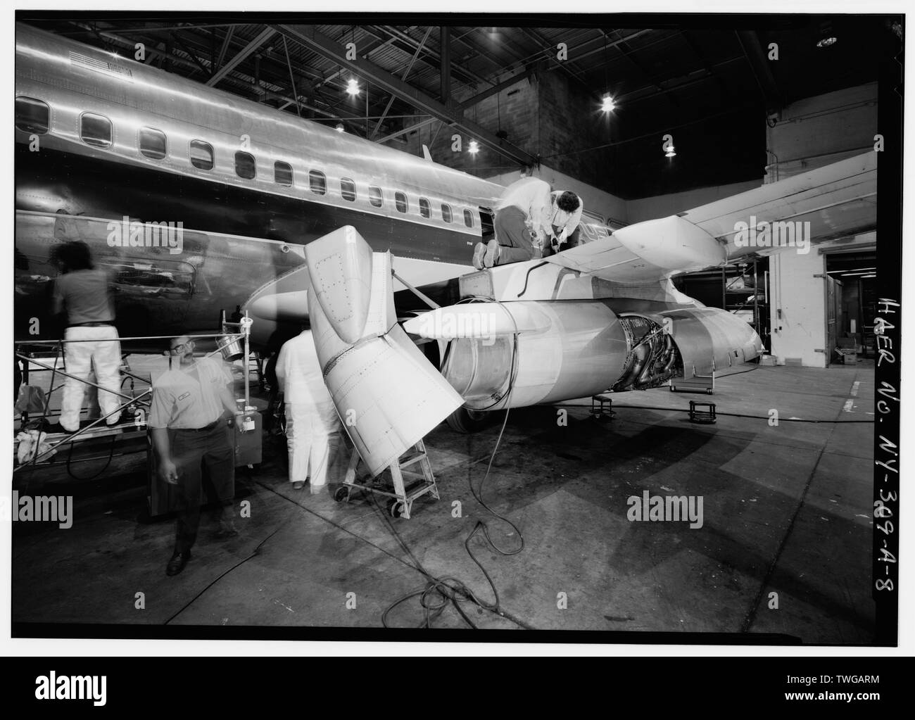 REAR DETAIL OF RIGHT ENGINE AND WING. THRUST REVERSER REMAINS OPEN. MECHANICS JONI BAINE (R) AND BILL THEODORE(L) OPEN FLAP CARRIAGE ACCESS WITH AN IMPACT GUN. THEY WILL CHECK TRANSMISSION FLUID AND OIL THE JACK SCREW. AT FAR LEFT UTILITY MECHANICS BEGIN BODY POLISHING. - Greater Buffalo International Airport, Maintenance Hangar, Buffalo, Erie County, NY - Stock Image
