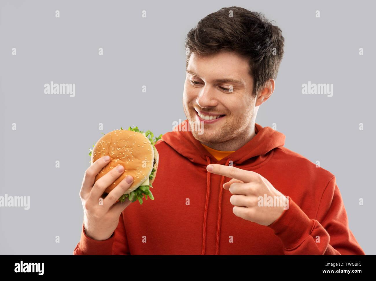 happy young man showing hamburger - Stock Image