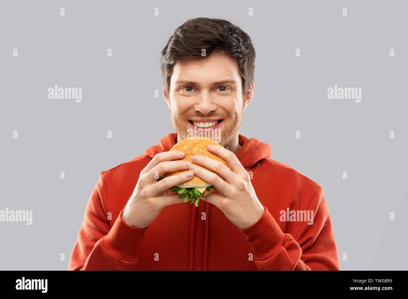 happy young man eating hamburger - Stock Image