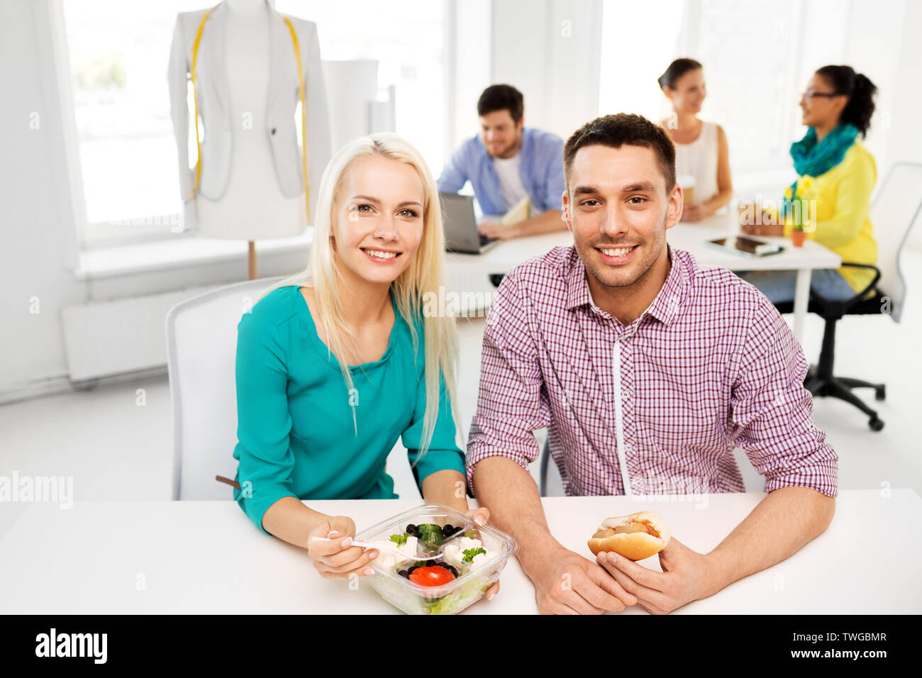 happy colleagues having lunch and eating at office - Stock Image