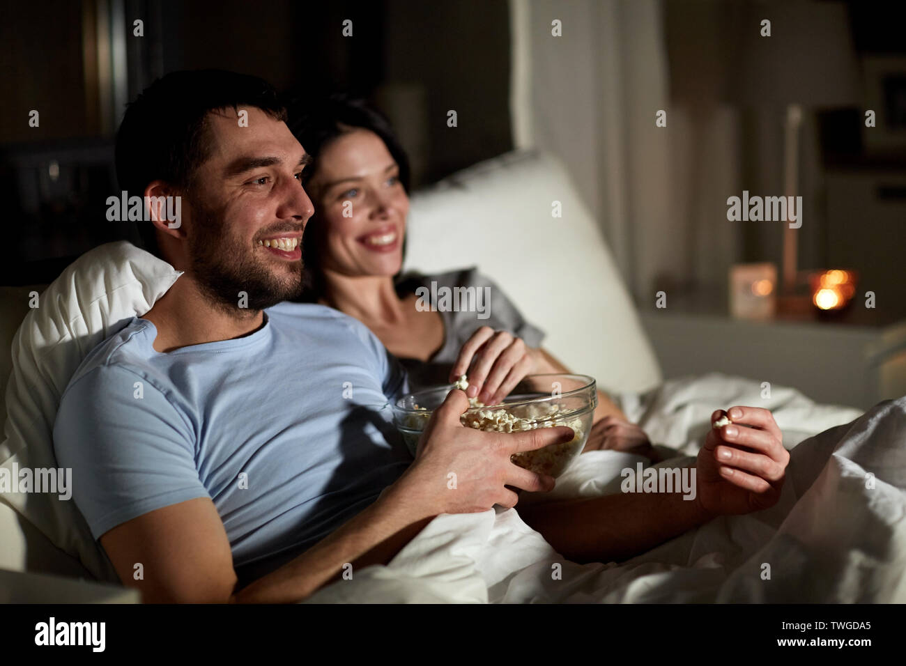 couple with popcorn watching tv at night at home - Stock Image