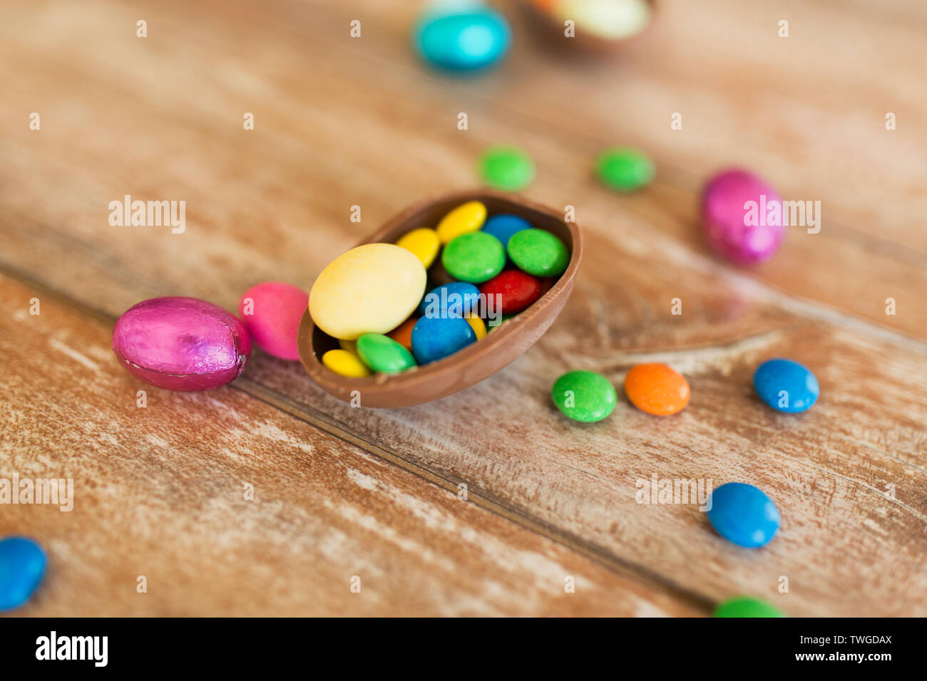 chocolate egg and candy drops on wooden table - Stock Image