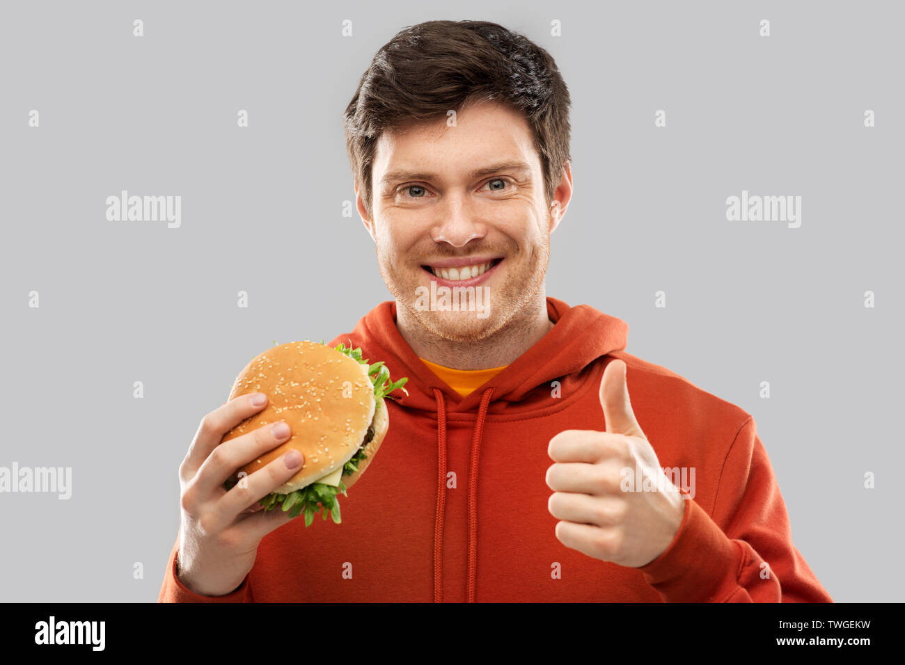happy young man with hamburger showing thumbs up - Stock Image