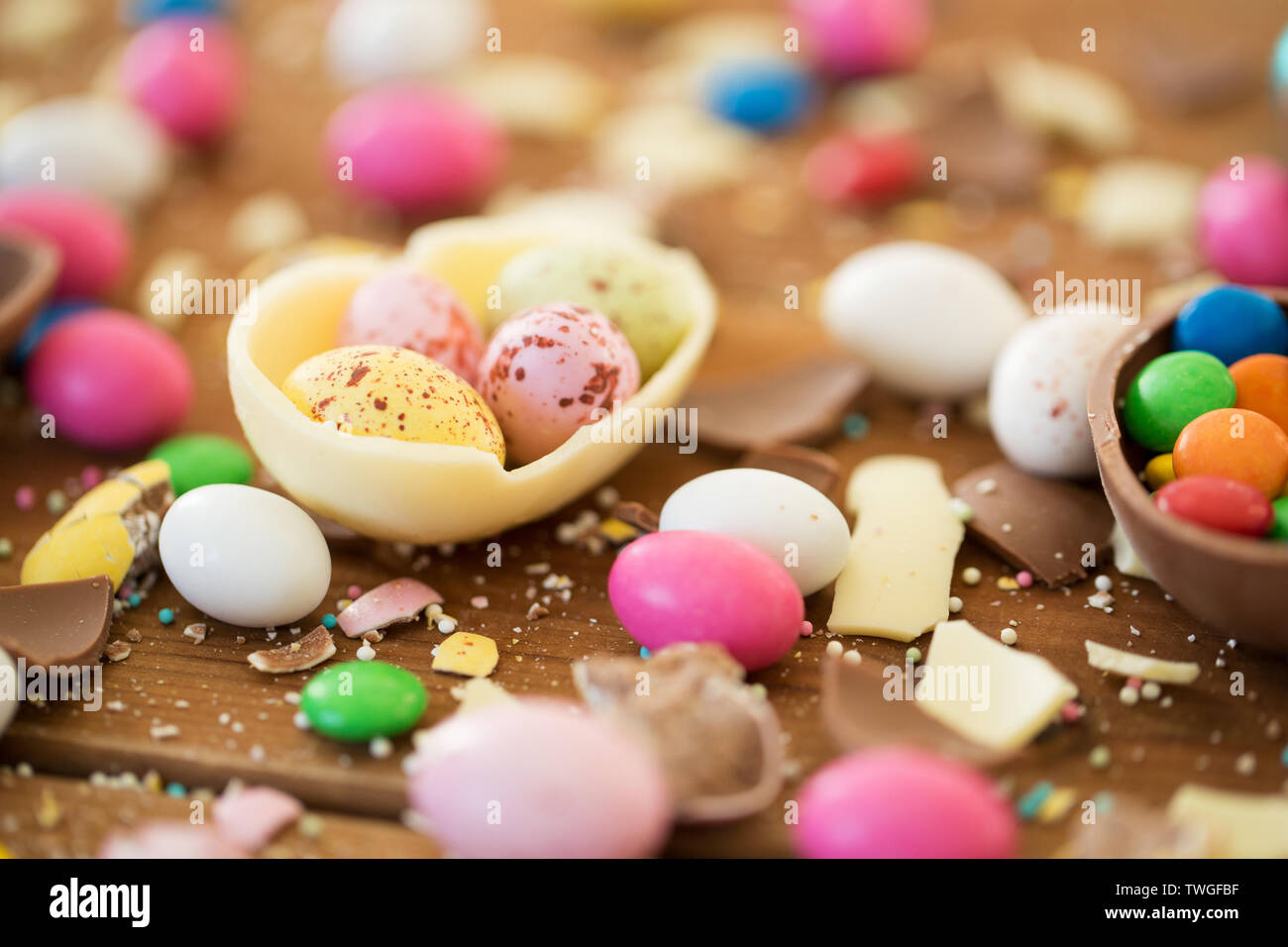 chocolate easter eggs and candy drops on table - Stock Image