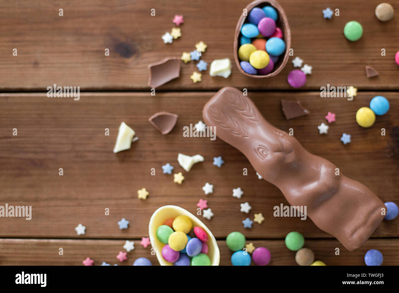 chocolate eggs, easter bunny and candies on wood - Stock Image