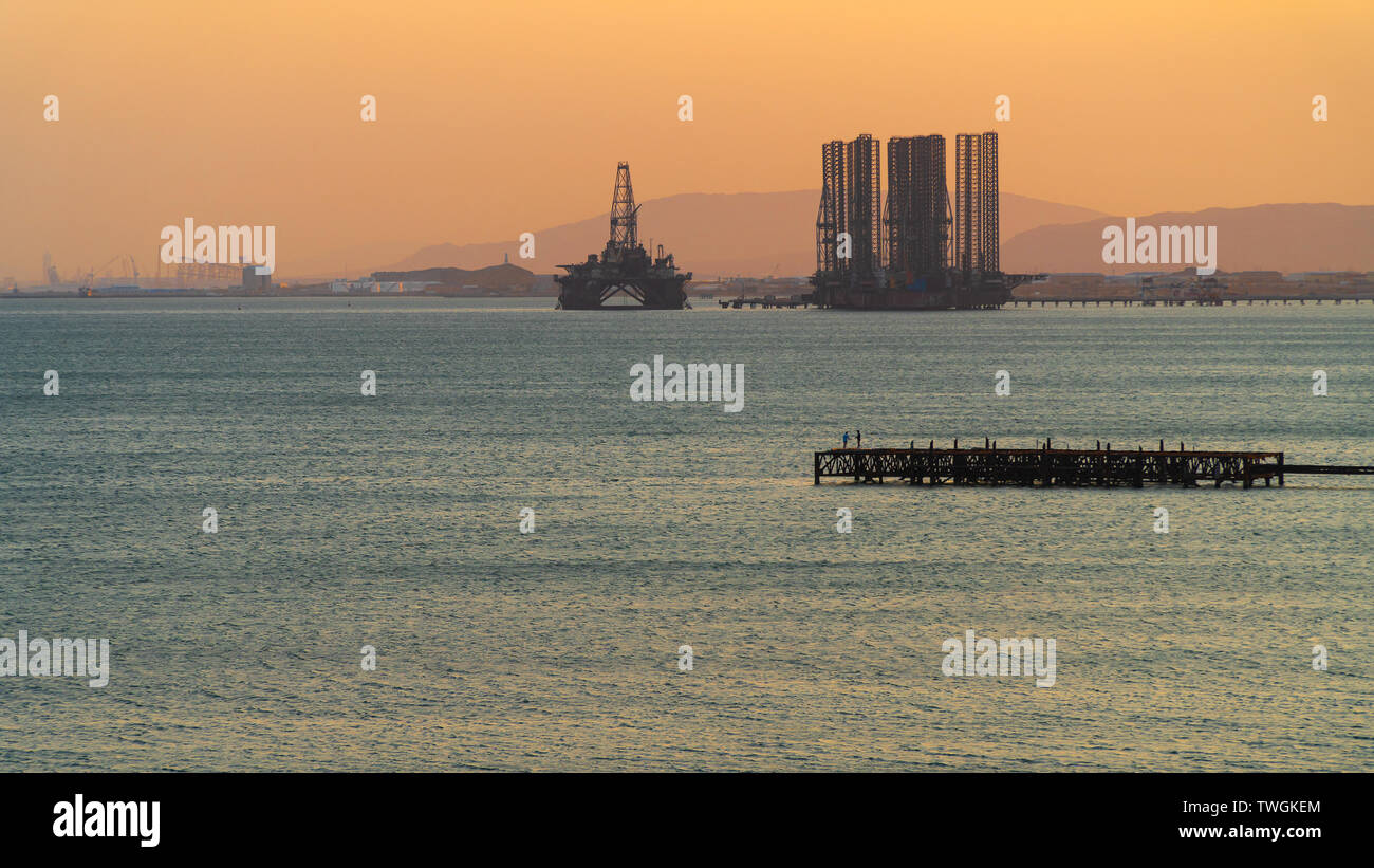Oil platforms in the sea at sunset - Stock Image