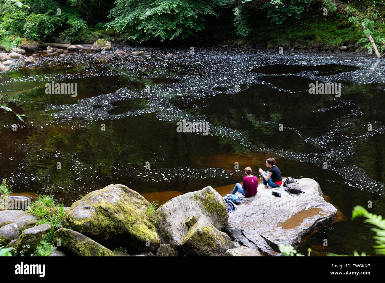 Two women sitting on riverbank of River Braan at The Hermitage in Perthshire, Scotland, UK - Stock Image