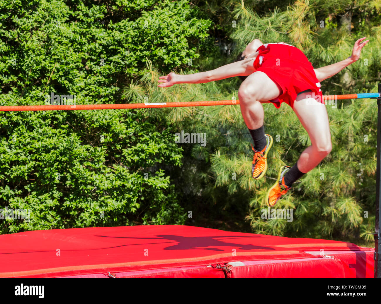 A male high school high jumper is over the bar with trees in the background. Stock Photo