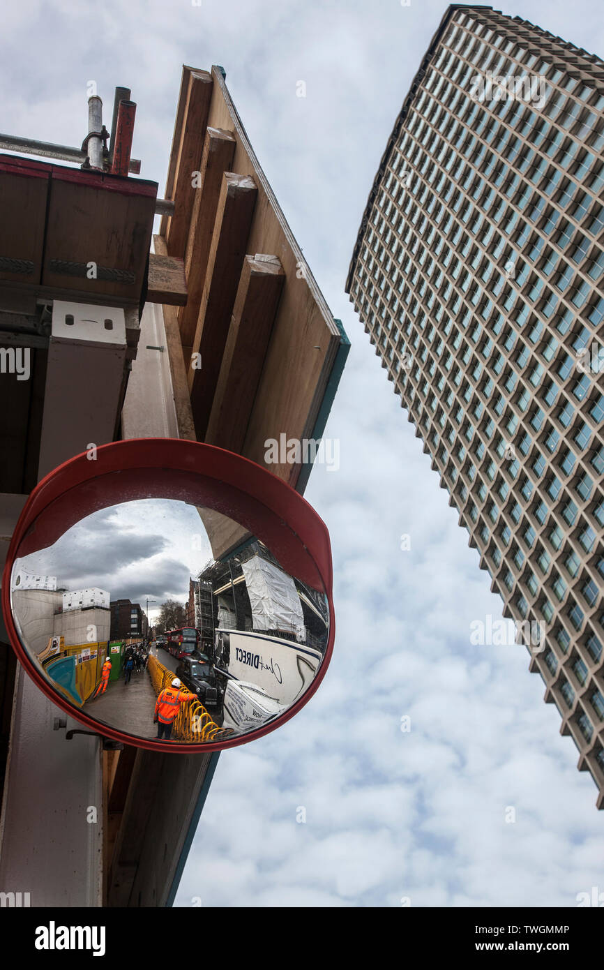 construction workers seen in convex mirror at tottenham court road crossrail works beside Centrepoint tower London, Stock Photo