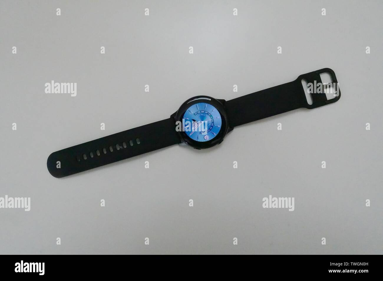 A black Samsung Galaxy Active smart watch displaying a standard watch face on a white background. - Stock Image