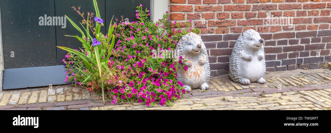 Two white smiling hedgehogs and flowers as decoration in the street in front of a house - Stock Image