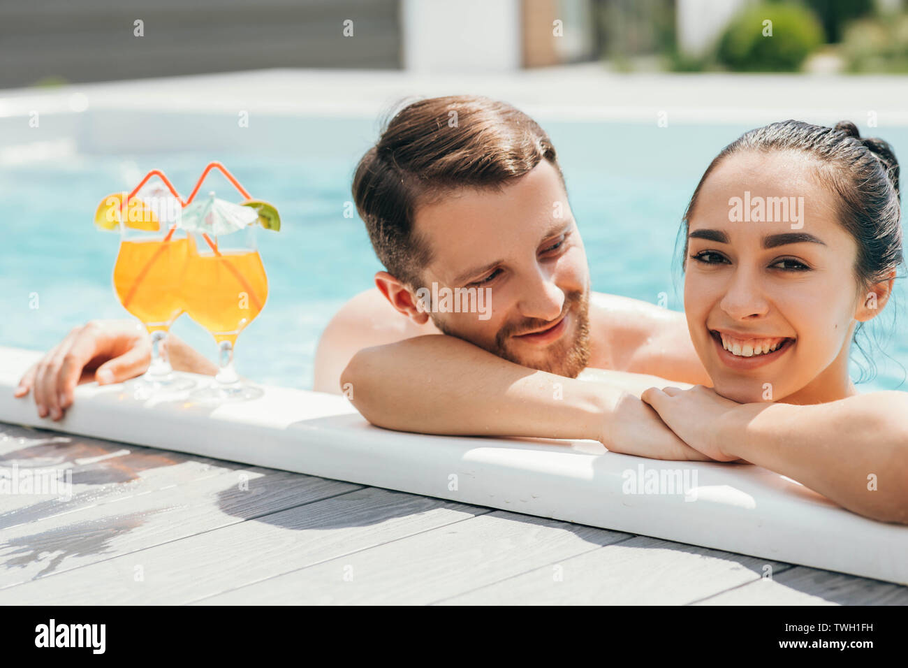 happy heterosexual couple is well rested with cocktails while in the pool. Summer rest Stock Photo