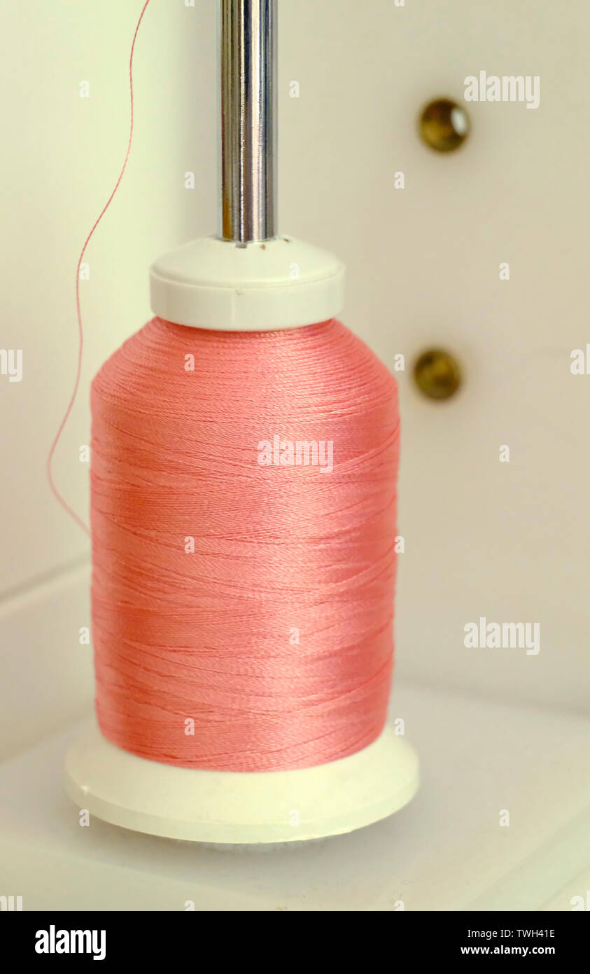 Peachy pink spool of machine embroidery thread on spindle - Stock Image