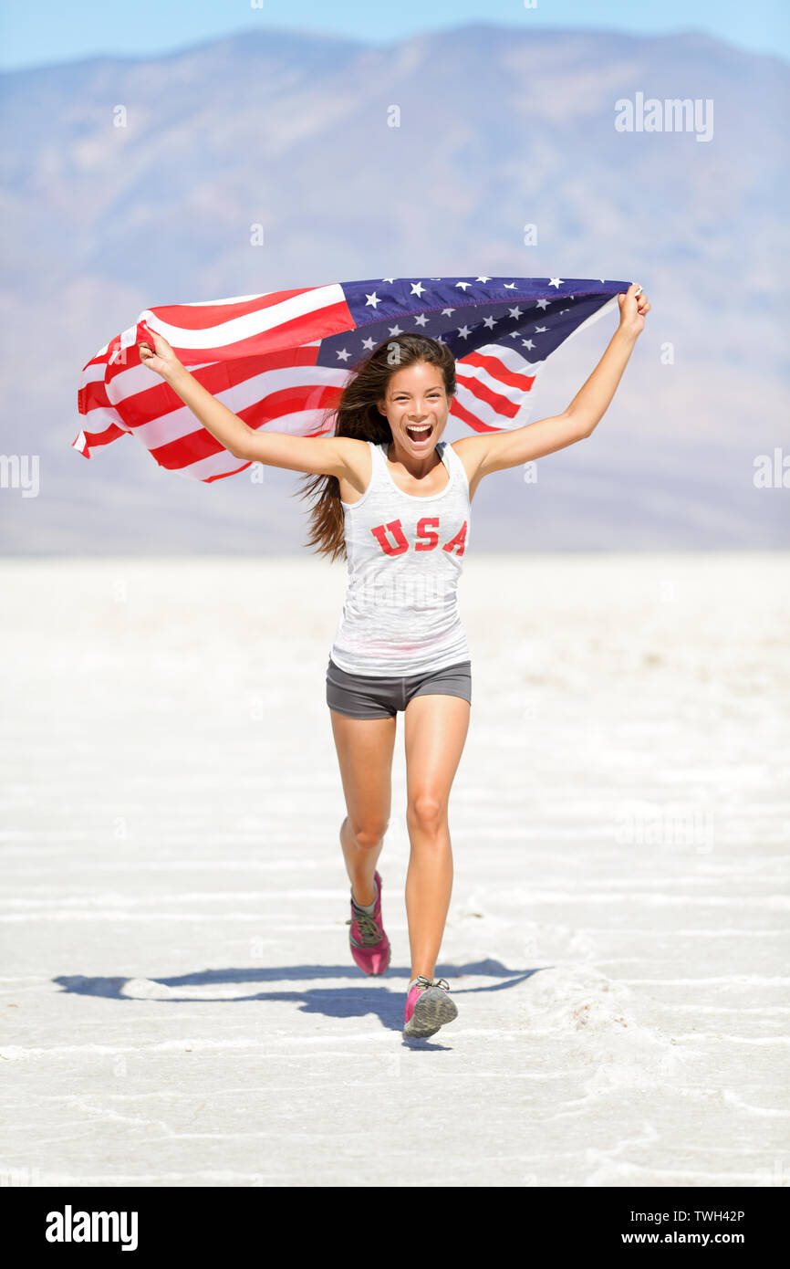 Athlete woman with american flag running with USA t-shirt showing winning gesture excited and happy outdoor in desert nature. Cheerful fitness woman winner cheering. - Stock Image