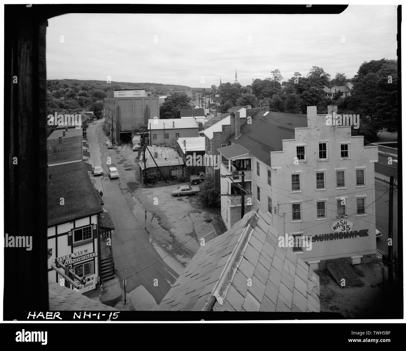 River Street from the cupola of the Sugar River Grist Mill, looking east. Tenements line the left side of the road and have no front yards or sidewalk. Warehouse No. 34, Sullivan Machinery Co., is on the right at the bend in River Street. - Claremont Village Industrial District, Between B, Claremont, Sullivan County, NH - Stock Image
