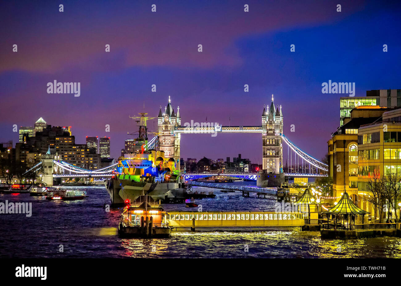 HMS Belfast and Tower Bridge on The River Thames lit up at night in London, UK on 16 December 2012 - Stock Image