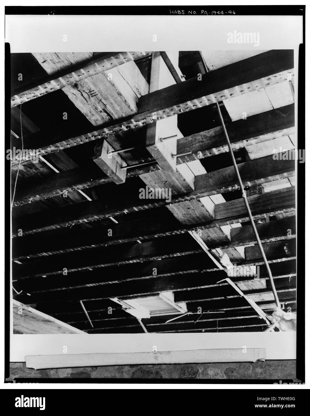 SECOND FLOOR CEILING FRAMING. The 1812 furring strips are still in place, fastened to the undersides of the 1755 joists. The joists frame into the bottom chords of the 1755 salvaged trusses. Note the numerals, VIII (8), N (9), X (10), and XI (11) on alternate panels of the bottom chord of the truss. Between the reinforcing plates note the numeral VII (7), added for the 1812 installation - Twelfth Street Meeting House, 20 South Twelfth Street, Philadelphia, Philadelphia County, PA - Stock Image
