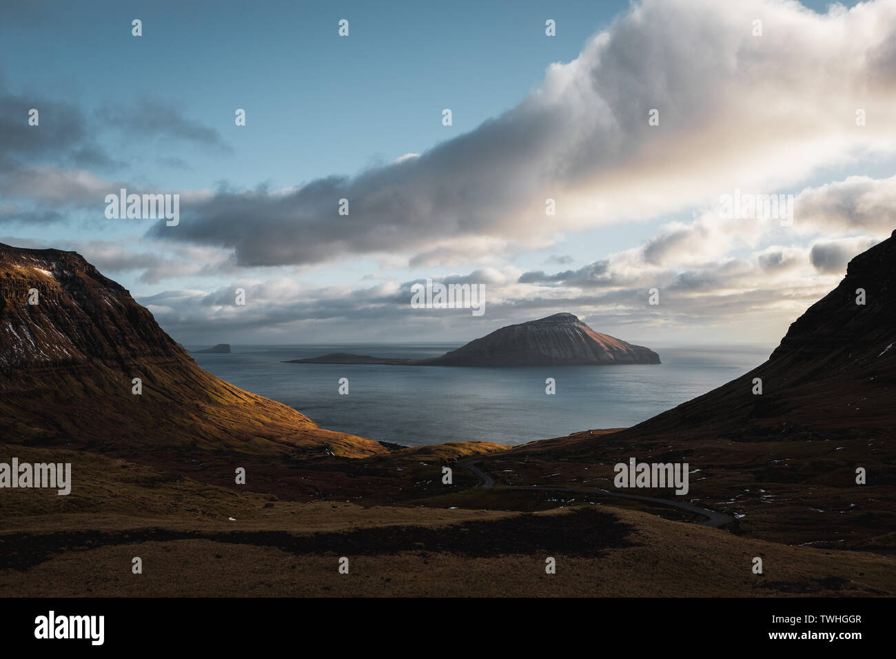 Evening views onto the Faroese island Koltur with spectacular clouds, low sun and blue sky in a dramatic valley with mountain range (Faroe Islands) - Stock Image