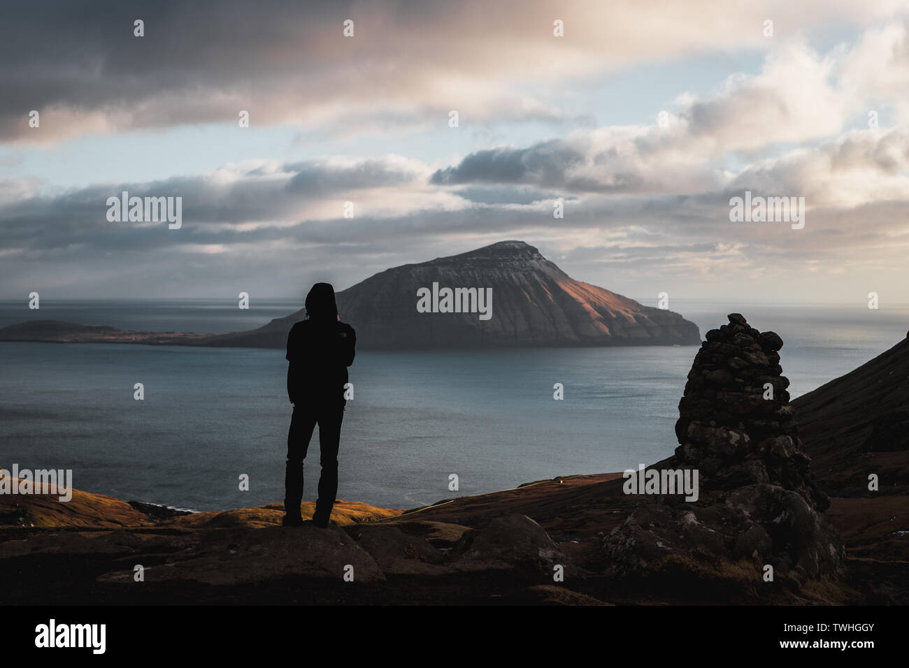 Lonely wanderer enjoying evening views onto the Faroese island Koltur with spectacular clouds, low sun, blue sky during early spring (Faroe Islands) - Stock Image