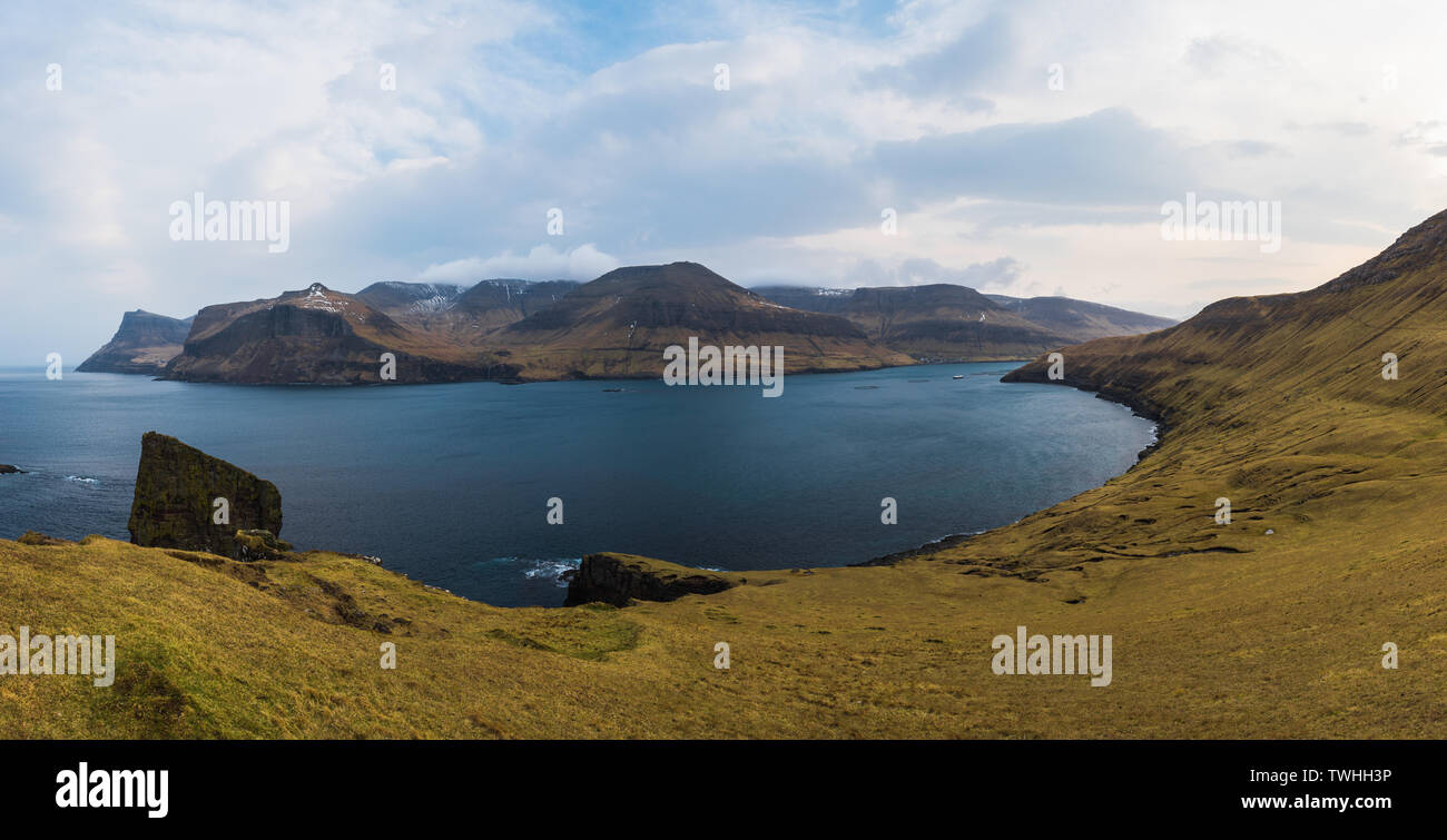 Panorama of hiking route towards Drangarnir and Tindholmur island taken during hike along the Faroese coastline with village Bour (Faroe Islands) - Stock Image