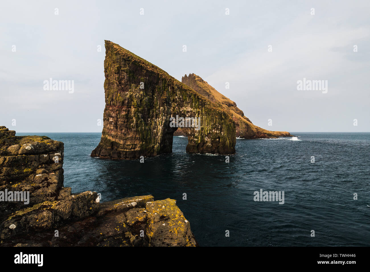 Close-up shot of famous Drangarnir cliff with Tindholmur islands in the background taken during early morning hike in spring (Faroe Island, Denmark) - Stock Image