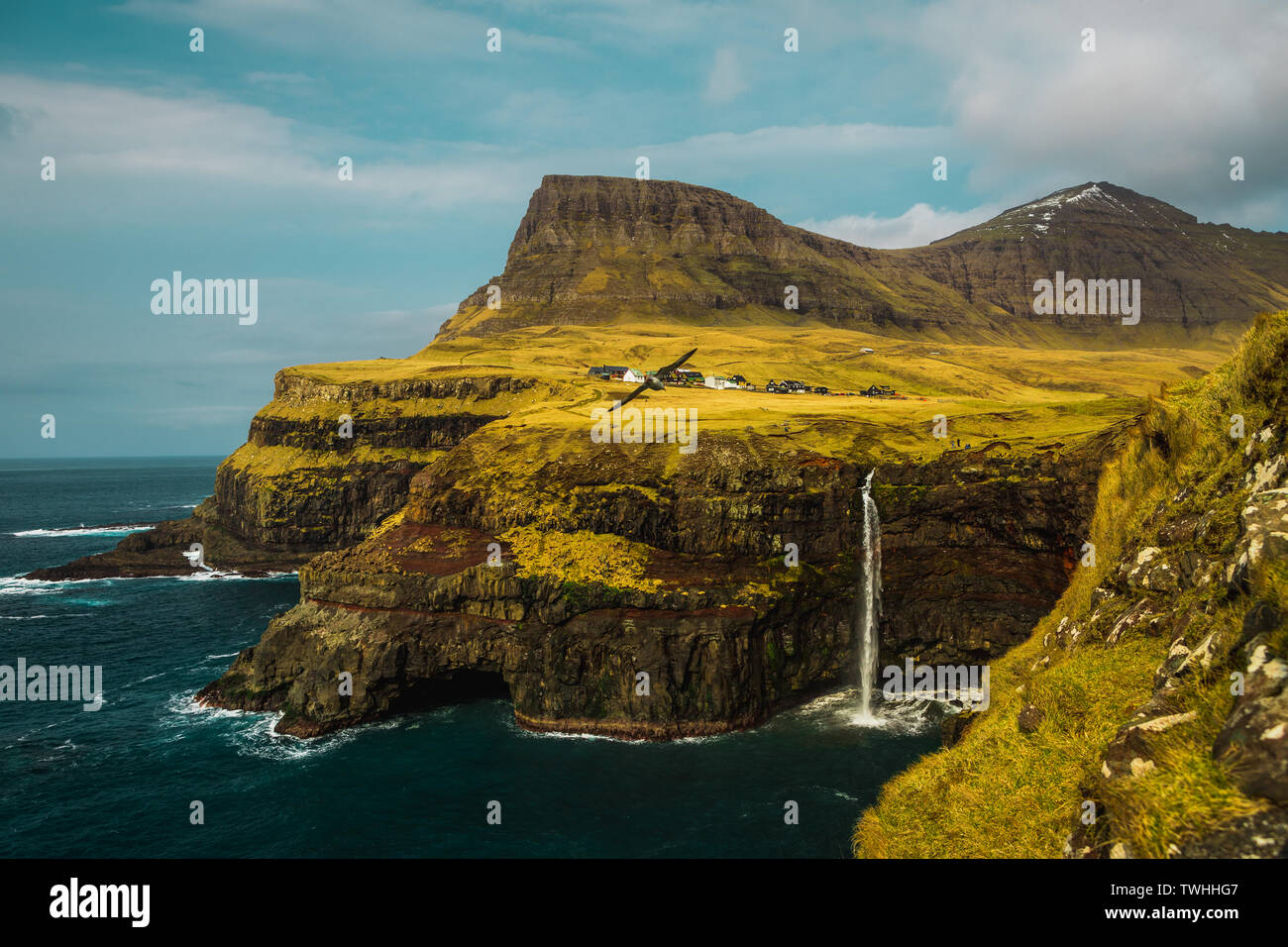 View onto famous Gasadalur waterfall from viewpoint during a sunny spring day with snow-covered mountain peaks and dark blue sea (Faroe Islands) - Stock Image