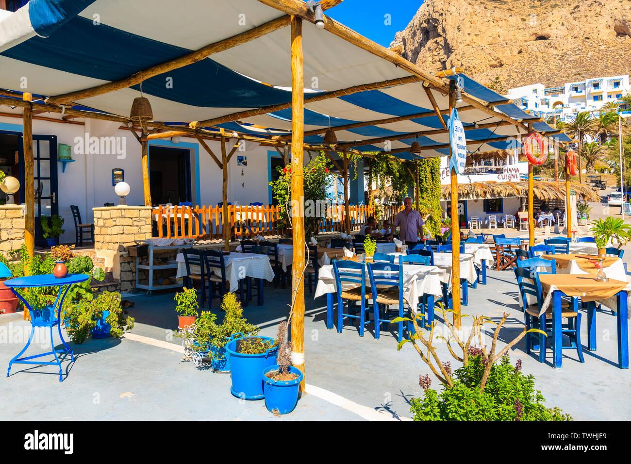 FINIKI PORT, KARPATHOS ISLAND - SEP 25, 2018: View of taverna restaurant in small fishing village on coast of Karpathos island, Greece. Stock Photo