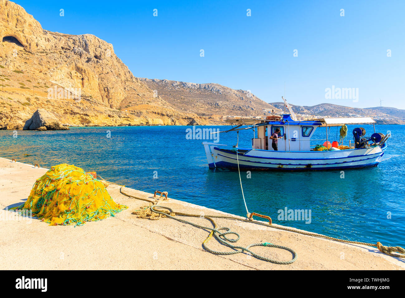 Fishing boat in picturesque Finiki port with mountains in background, Karpathos island, Greece Stock Photo