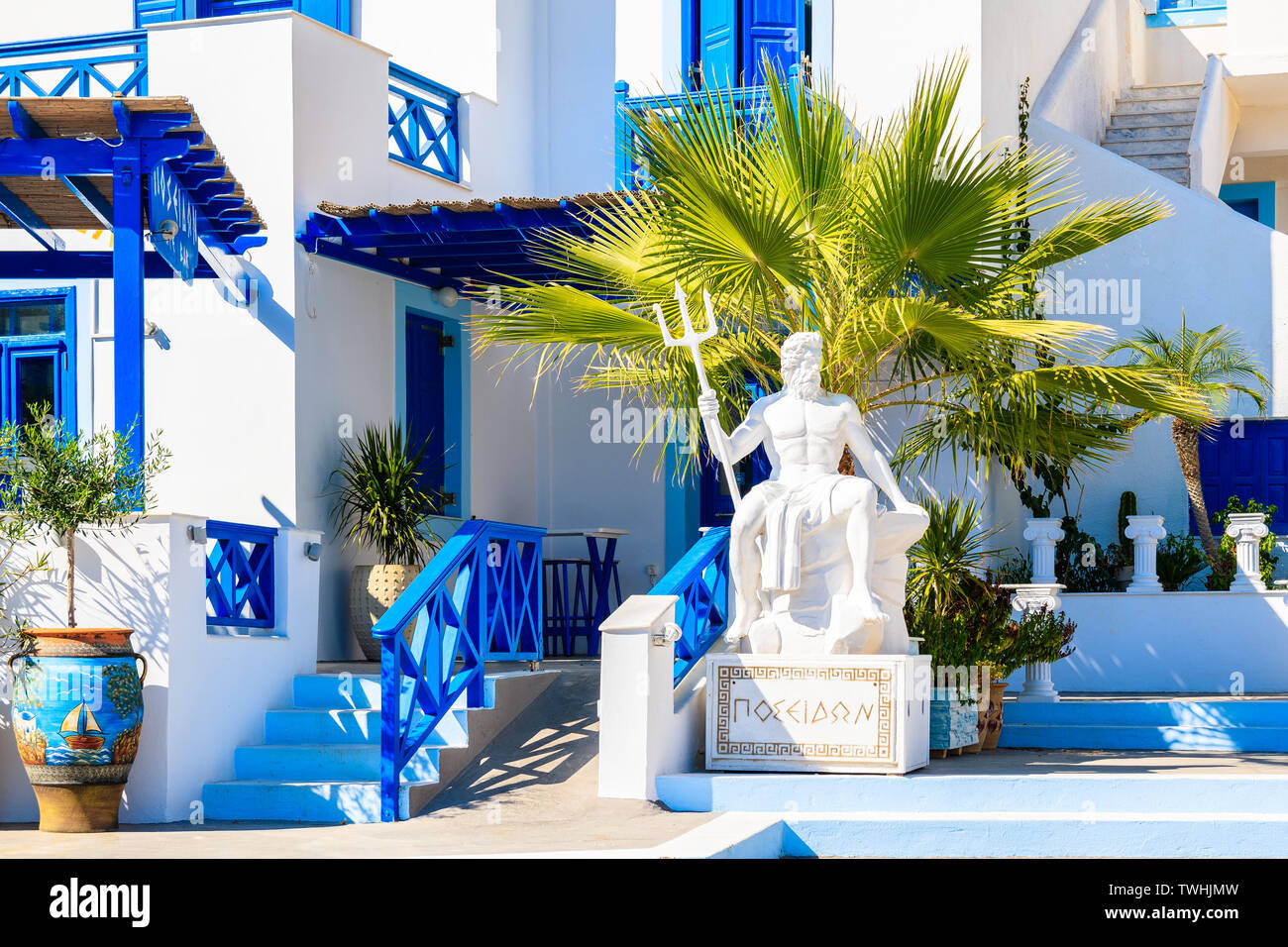 """FINIKI PORT, KARPATHOS ISLAND - SEP 25, 2018: Sculpture of """"Poseidon"""" - god of the sea in ancient Greek religion and myth in front of typical building Stock Photo"""