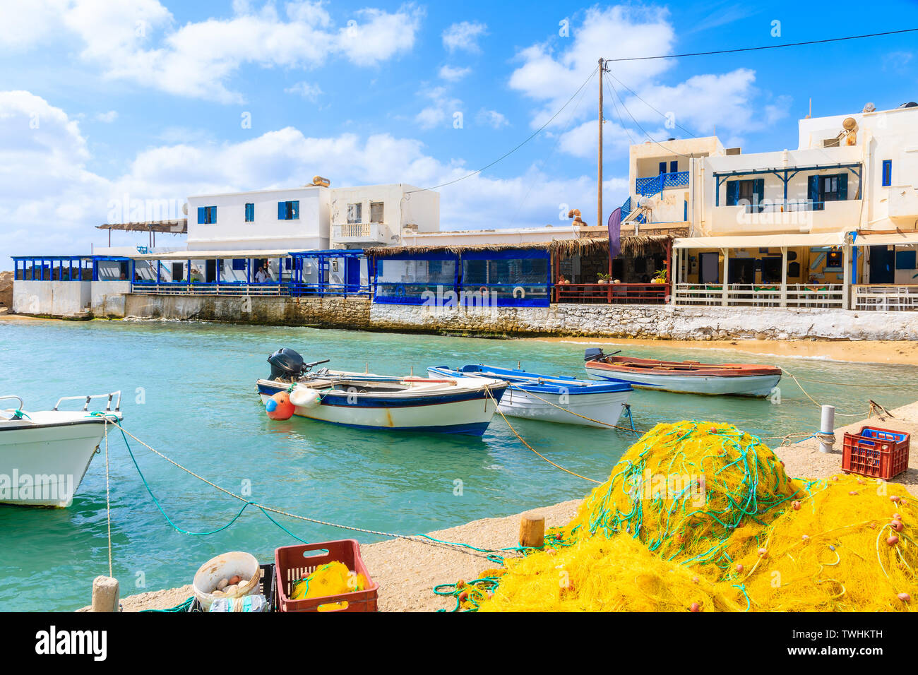 Fishing boats in Lefkos port with tavernas in background, Karpathos island, Greece Stock Photo