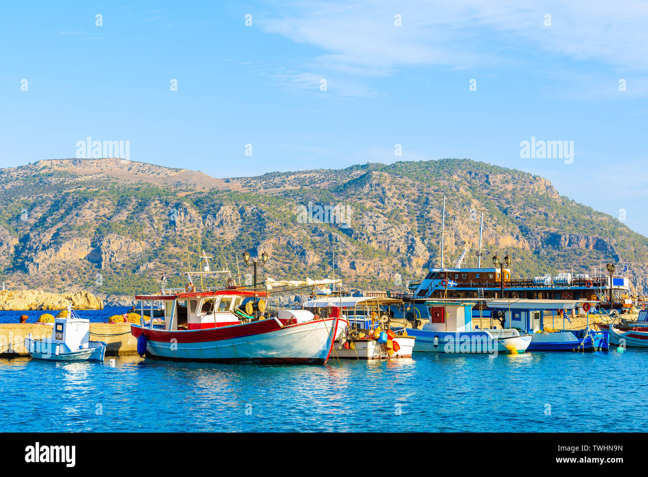 Boats in beautiful Pigadia fishing port with mountains in background, Karpathos island, Greece Stock Photo