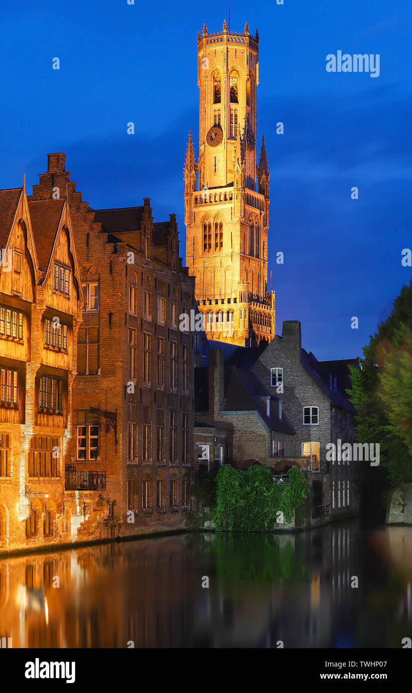 Famous view of Bruges tourist landmark attraction - Rozenhoedkaai canal with Belfry and old houses along canal with tree in the night. Bruges, Belgium - Stock Image