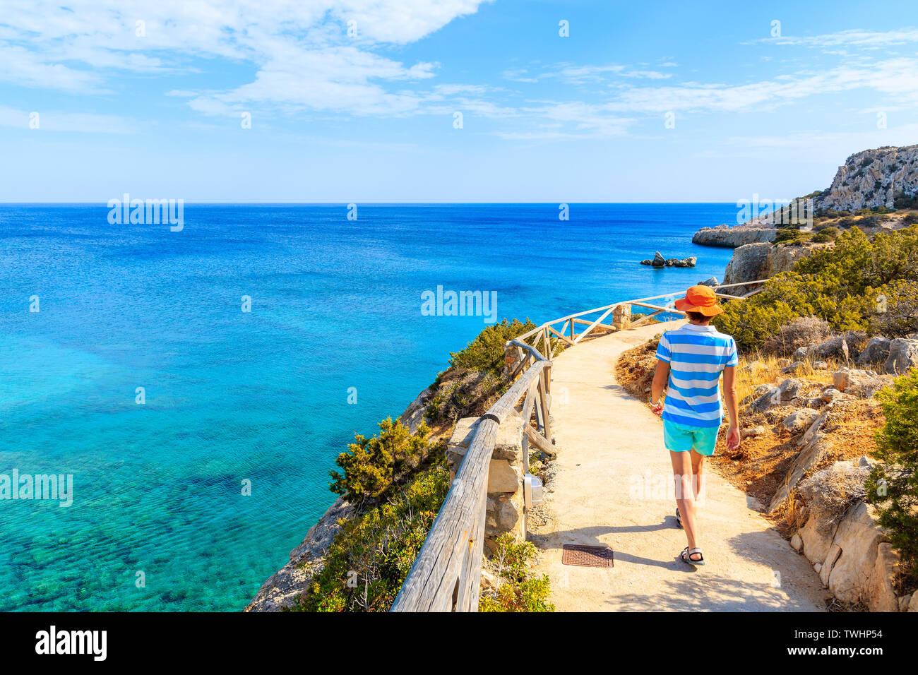 Young woman walking on coastal path along sea near Ammopi village, Karpathos island, Greece Stock Photo