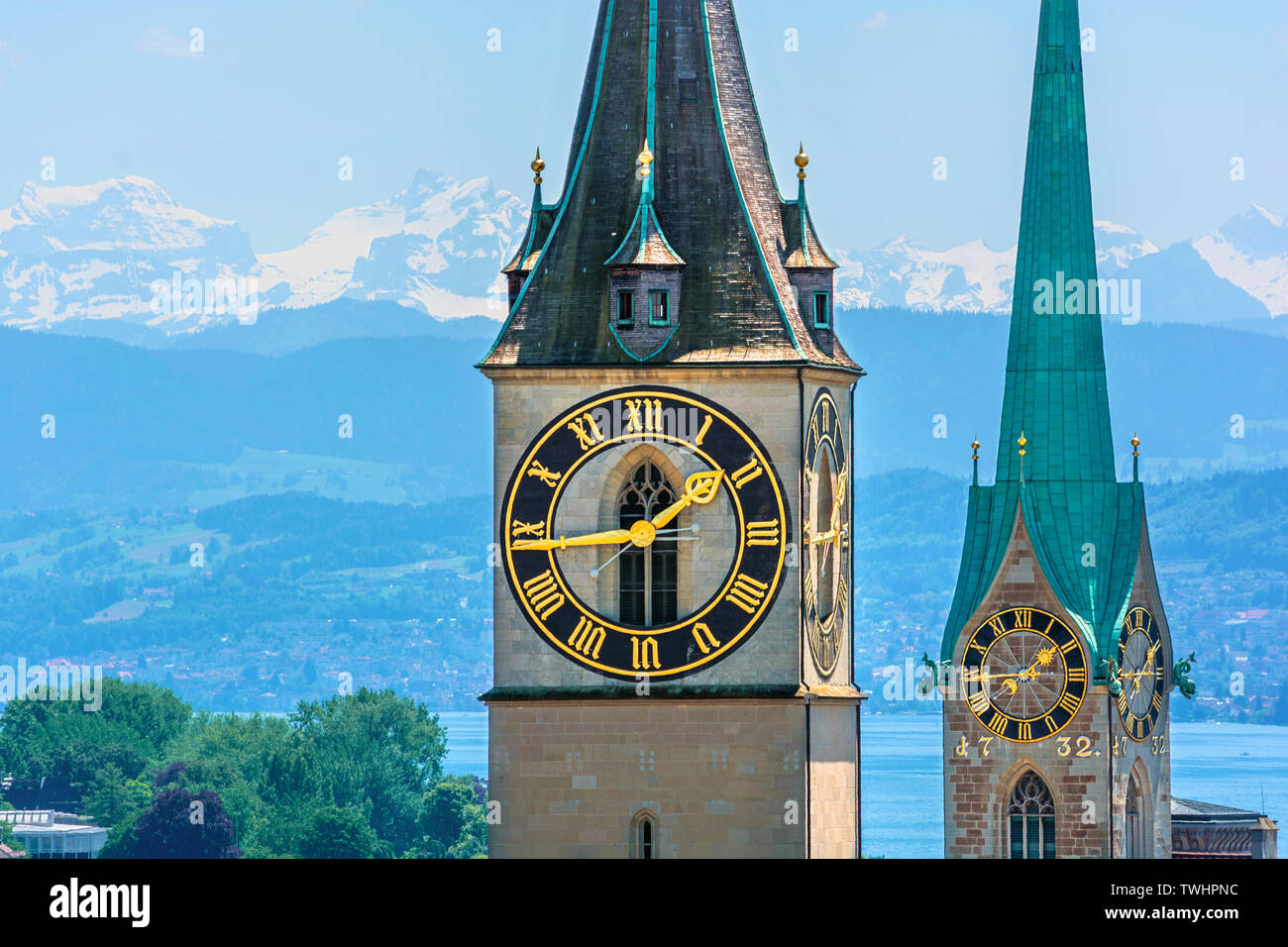 Saint Peter and Fraumünster Church in Zurich (Switzerland) in front of lake Zurich and the Swiss Alps - Stock Image