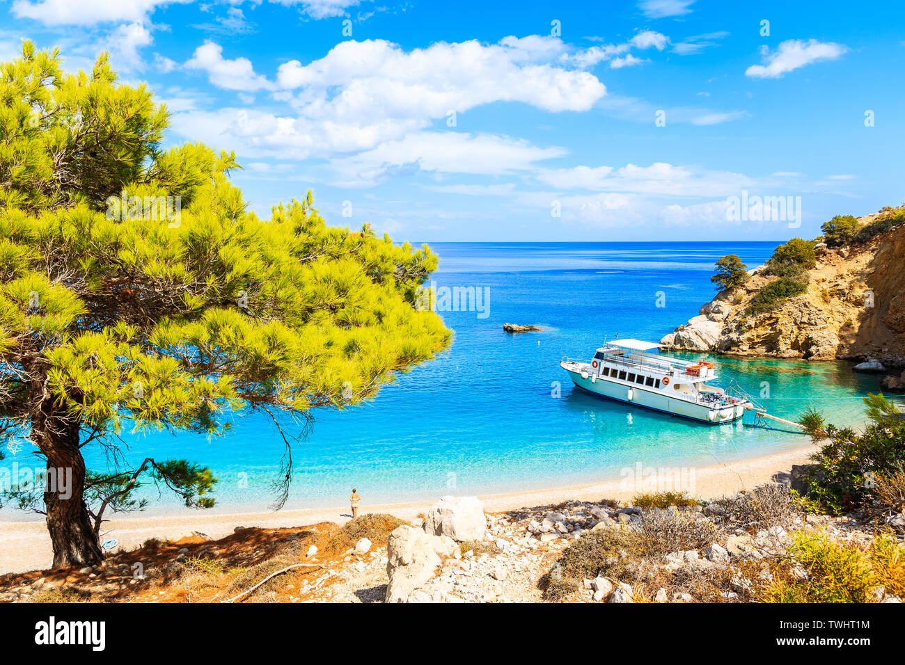 Tourist boat anchoring at beautiful Apella beach on Karpathos island, Greece Stock Photo