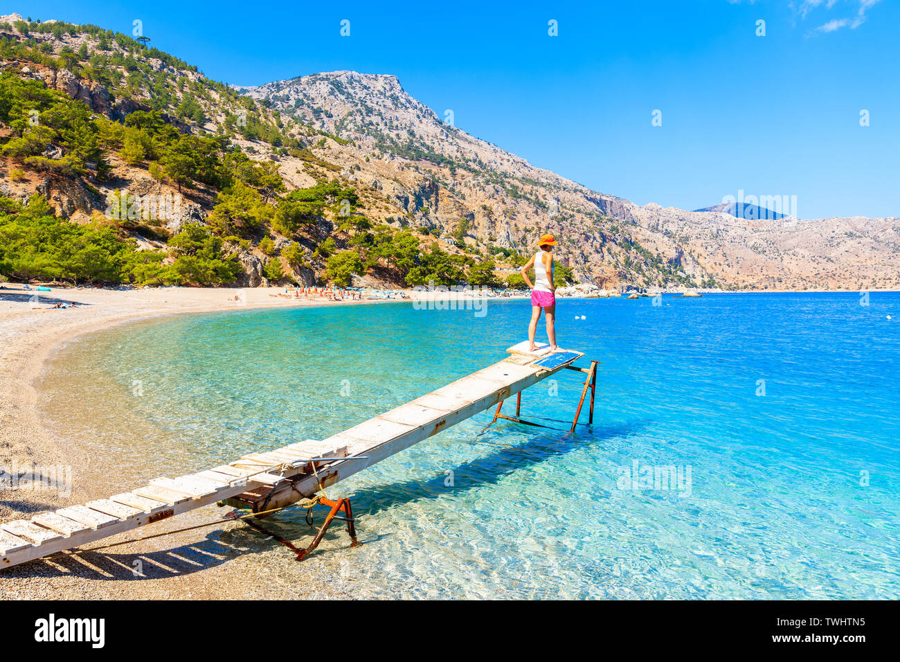 Young woman standing on small wooden jetty at Apella beach, Karpathos island, Greece Stock Photo